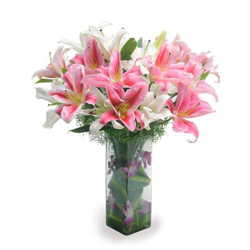 10 Oriental Lilies With Some Orchid Petals And Green Leaves In A Glass Vase